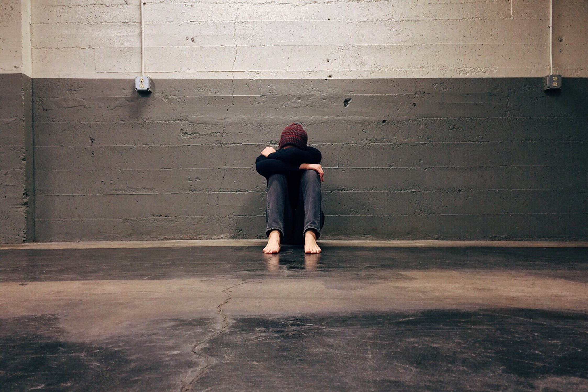 anxiety sufferer with head down leaning against the wall